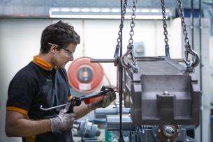 Apprentice engineer applying sealant to industrial gearbox in factoryの写真素材 [FYI03802153]