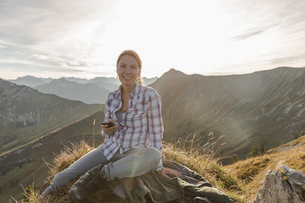 Portrait of a mid adult woman backpacker with smartphone, Achensee, Tyrol, Austriaの写真素材 [FYI03802280]
