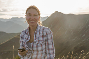 Portrait of a mid adult woman backpacker with cellphone, Achensee, Tyrol, Austriaの写真素材 [FYI03802283]