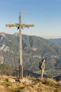 Mid adult woman backpacker and wooden cross, Achensee, Tyrol, Austriaの写真素材 [FYI03802288]