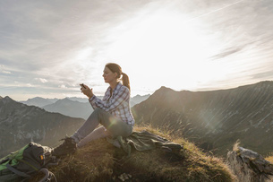 Portrait of a mid adult woman backpacker using smartphone, Achensee, Tyrol, Austriaの写真素材 [FYI03802290]