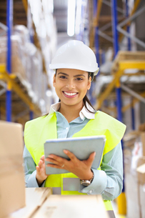 Young woman with digital tablet in distribution warehouseの写真素材 [FYI03802454]