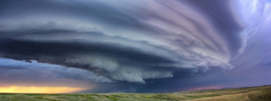 Large arcus cloud sweeps around the updraft of anticyclonic supercell with sunset colors projected oの写真素材 [FYI03802621]