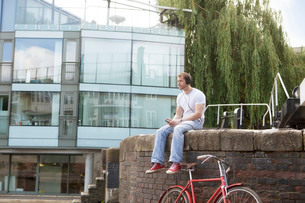 Man listening to music by canal, East London, UKの写真素材 [FYI03802633]