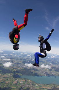 Team of two female skydivers in sit fly and head down positions over Buttwil, Luzern, Switzerlandの写真素材 [FYI03802657]