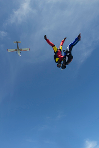 Team of two female skydivers in head down position over Buttwil, Luzern, Switzerlandの写真素材 [FYI03802670]