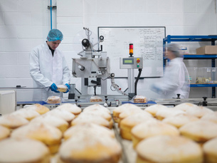 Male baker putting cakes on packaging line in cake factoryの写真素材 [FYI03802684]