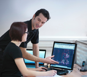 Office workers looking at CAD drawings in carbon fibre factoryの写真素材 [FYI03802777]