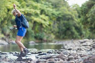 Hiker walking among stones in shallow stream, Waima Forest, North Island, NZの写真素材 [FYI03802780]
