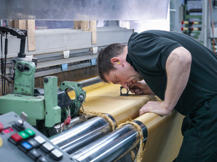 Worker inspecting kevlar fabric in carbon fibre factoryの写真素材 [FYI03802784]