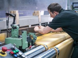 Worker weaving kevlar fabric in carbon fibre factoryの写真素材 [FYI03802791]
