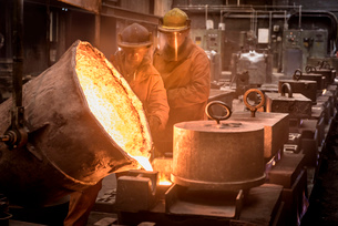 Two workers pouring molten metal from flask in foundryの写真素材 [FYI03802838]