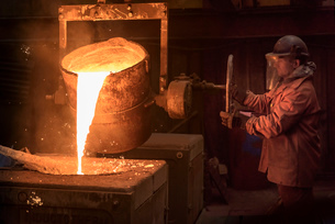 Worker pouring molten metal from flask in foundryの写真素材 [FYI03802840]