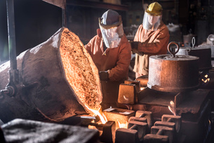 Workers pouring molten metal from flasks into moulds in foundryの写真素材 [FYI03802842]
