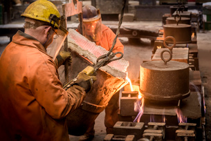 Workers pouring molten metal from flask in foundryの写真素材 [FYI03802843]
