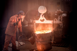 Worker with flask of molten metal in foundryの写真素材 [FYI03802848]