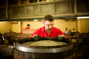 Male cooper working in cooperage with whisky caskの写真素材 [FYI03802916]