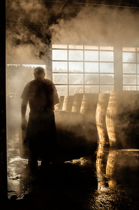 Male cooper working in cooperage with whisky casksの写真素材 [FYI03802928]