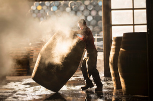 Male cooper working in cooperage with whisky casksの写真素材 [FYI03802929]