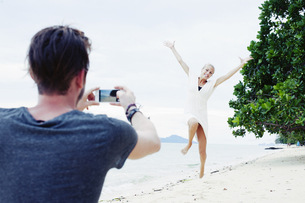 Young man photographing girlfriend jumping on beach, Kradan, Thailandの写真素材 [FYI03802972]