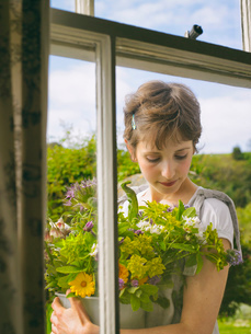 Young woman outside window with a bowl of wildflowersの写真素材 [FYI03803093]