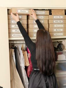 Corset maker arranging boxes in wardrobeの写真素材 [FYI03803174]