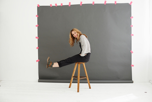 Woman on stool in front of photographers backdropの写真素材 [FYI03803196]