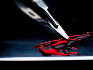 Surgeons scalpel sitting in tray with bloodの写真素材 [FYI03803237]