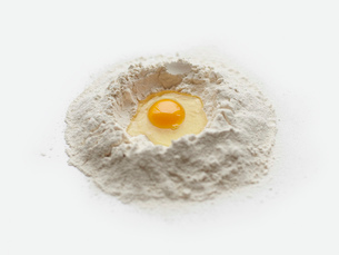 Baking preparation with raw egg in center of flour stackの写真素材 [FYI03803255]