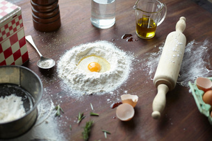 Table with raw egg in center of flour stack and kitchen utensilsの写真素材 [FYI03803257]