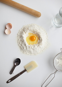 Overhead view with raw egg in center of flour stack and kitchen utensilsの写真素材 [FYI03803262]