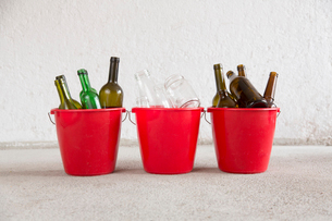 Three recycling buckets in garage with green, brown and transparent bottlesの写真素材 [FYI03803273]