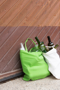 Two reusable shopping bags full of bottles for recycling in yardの写真素材 [FYI03803275]