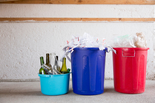 Three recycling buckets in garage with bottles, paper and plasticの写真素材 [FYI03803276]