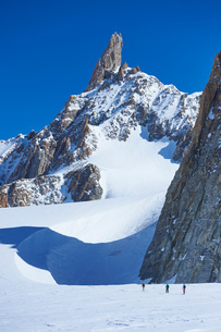 Distant view of three skiers on Mont Blanc massif, Graian Alps, Franceの写真素材 [FYI03803319]