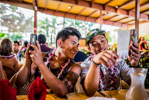 Two young men reading menu in Polynesian Cultural Centre, Hawaii, USAの写真素材 [FYI03803334]