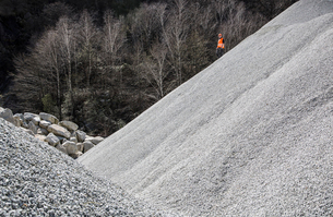 Quarry worker on gravel mound at quarryの写真素材 [FYI03803346]