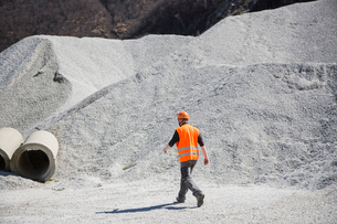 Quarry worker walking through gravel mounds at quarryの写真素材 [FYI03803353]