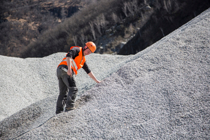 Quarry worker measuring on gravel mound at quarryの写真素材 [FYI03803354]