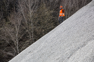 Quarry worker moving down gravel mound at quarryの写真素材 [FYI03803356]