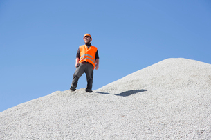 Quarry worker looking out from gravel mound at quarryの写真素材 [FYI03803357]