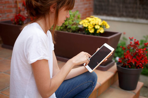 Side view of mid adult woman sitting outdoors using digital tabletの写真素材 [FYI03803367]