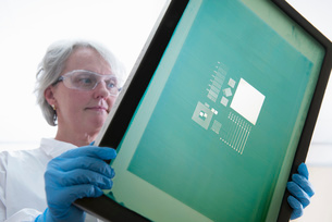 Scientist inspects screen printer mesh for graphene ink in graphene processing factory, close upの写真素材 [FYI03803487]
