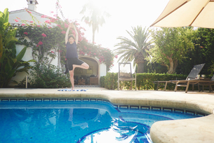 Mature woman in yoga pose at holiday apartment poolsideの写真素材 [FYI03803533]