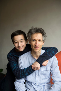 Portrait of teenage boy with arms around father on sofaの写真素材 [FYI03803570]