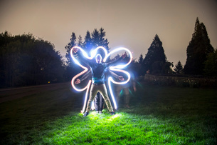 Two men standing together in field at dusk, creating star shape with bodies, friend tracing body shaの写真素材 [FYI03803712]