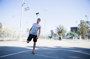 Young male basketball player doing warm up stretches on basketball courtの写真素材 [FYI03803732]