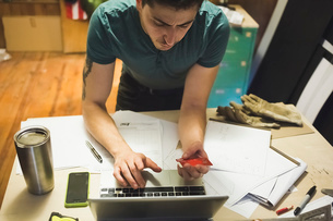High angle view of young man using credit card and laptop to make online purchaseの写真素材 [FYI03803790]