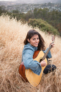 Portrait of young woman playing acoustic guitar on grassy hillの写真素材 [FYI03803840]