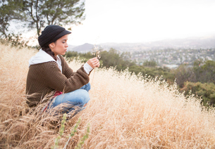 Young woman crouching on grassy hill holding dry blade of grassの写真素材 [FYI03803845]